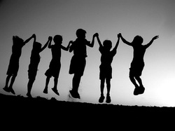 Silhouettes of children holding hands and jumping