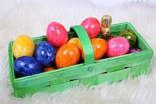 green rectangular basket filled with colorful eggs and chocolate bunny witting atop a white fur rug